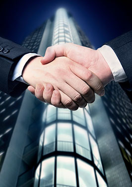 photo of handshake in front of large corporate building representing real estate attorney agreement