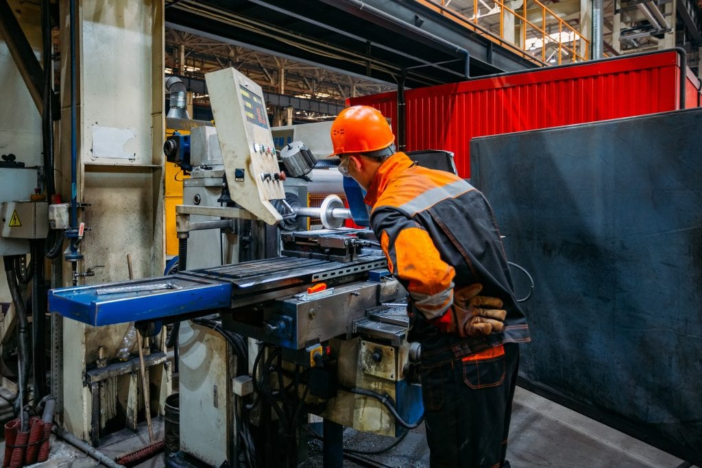 Male worker leaning over CNC machine watching fabrication process