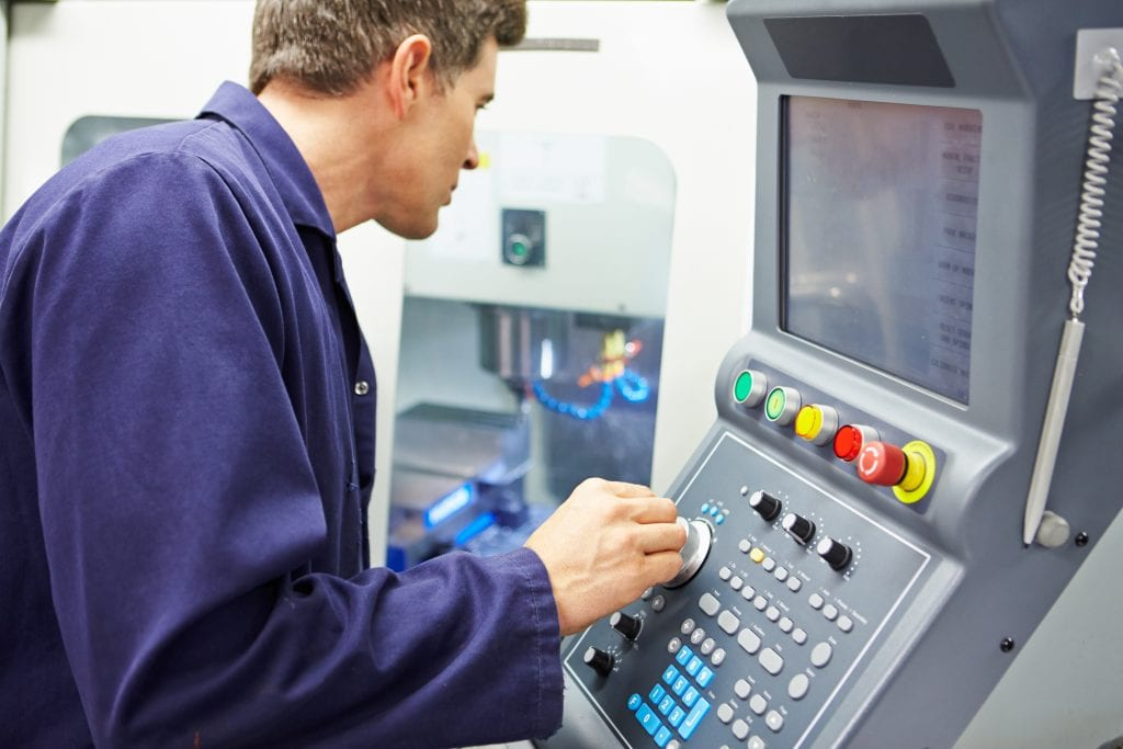 Man standing in front CNC milling machine control panel adjusting dials