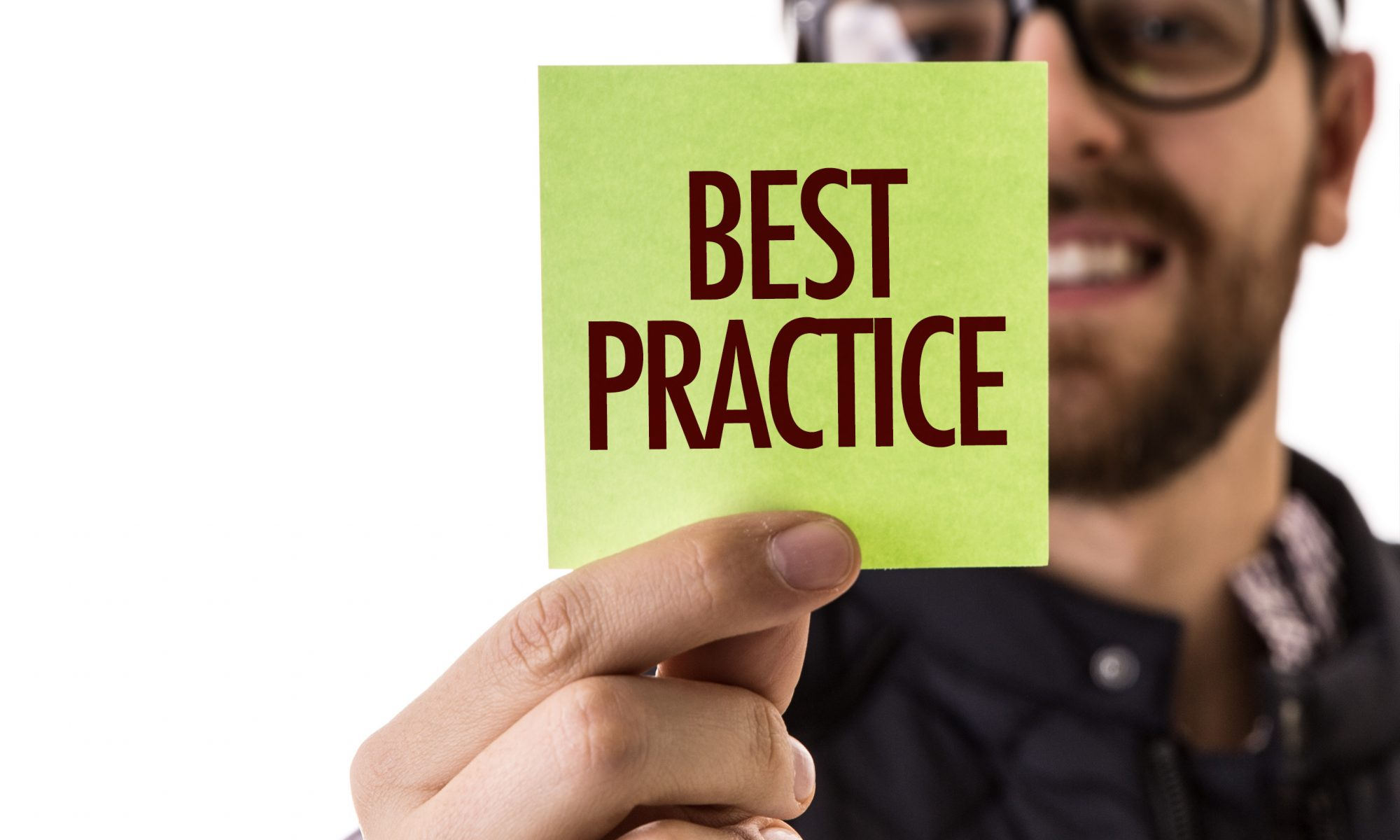 """A man holding up a yellow post-it with the word """"best practice"""" on it."""