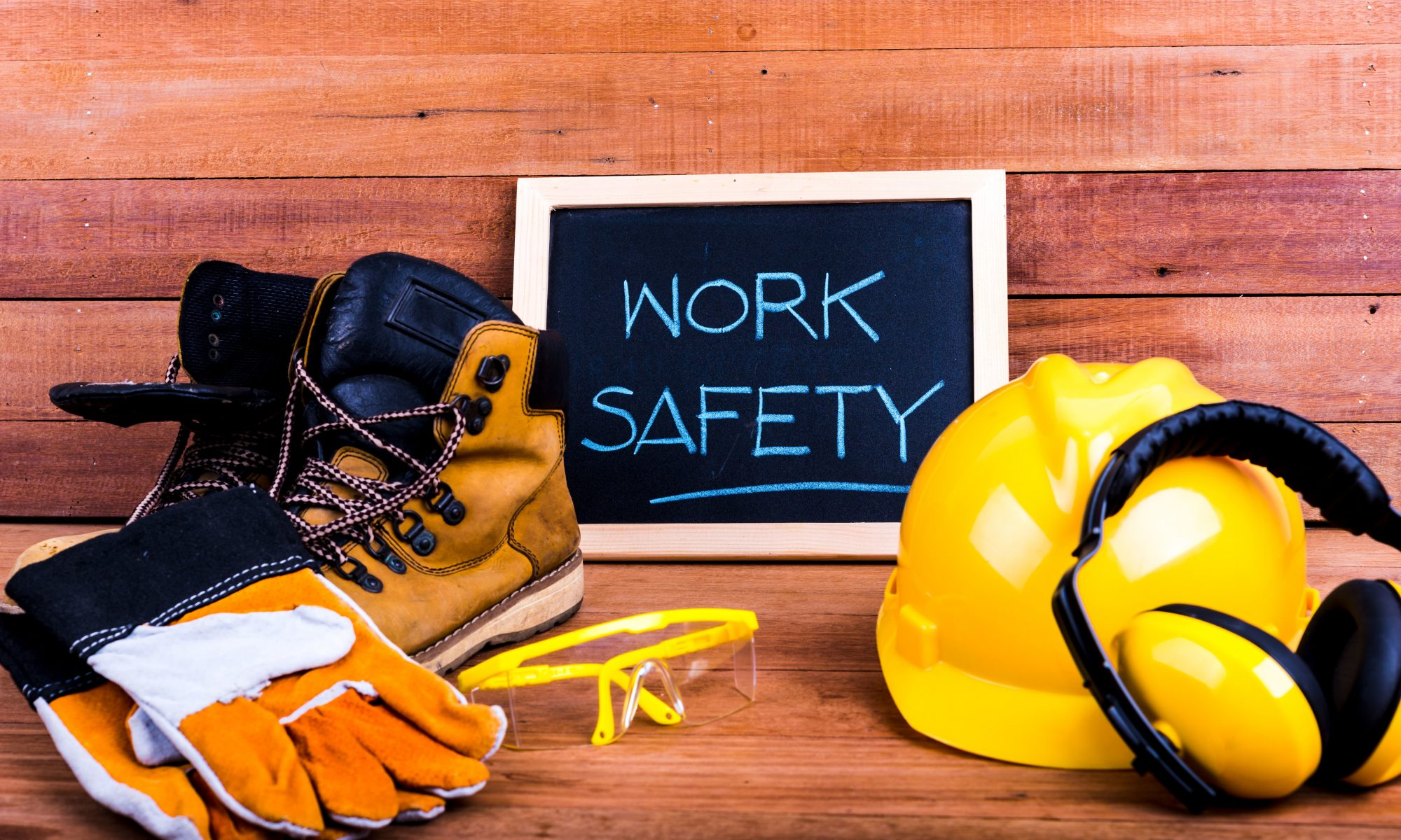"""gloves, work boots, safety goggles, hard hat on a wood plank background w/ """"work safety"""" written on a framed chalkboard"""