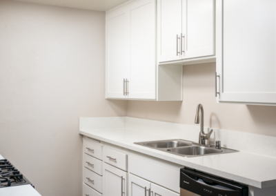 Kitchen with white cabinets and countertops and silver appliances