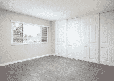 Empty bedroom with closets and window