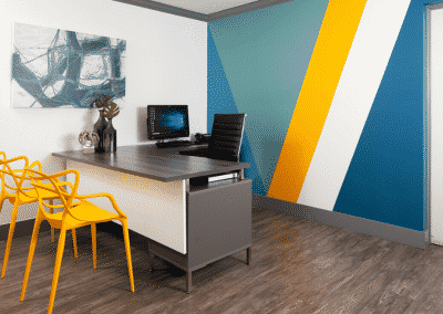 Leasing office with yellow chairs and bright wallpaper