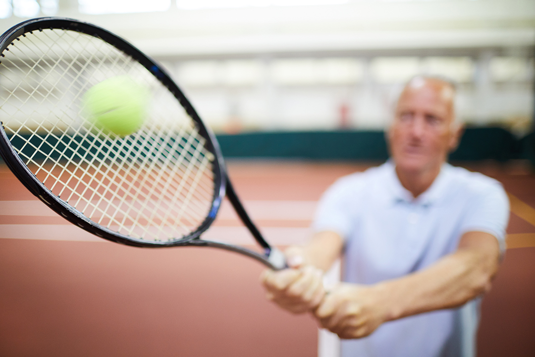 Elderly man hitting a tennis ball woth a racquet