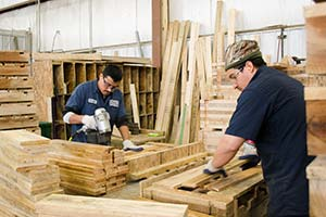 Workers making pallets and containers by hand.