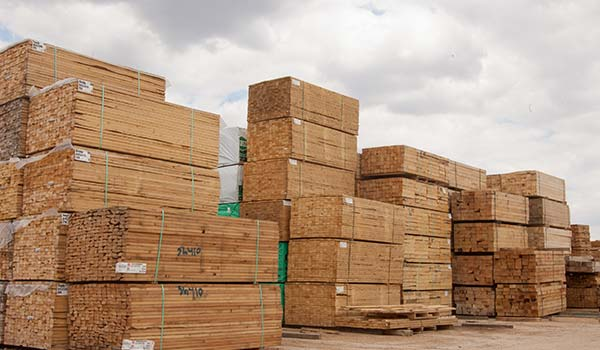 Photograph of large stacks of lumber in an outdoor storage area.