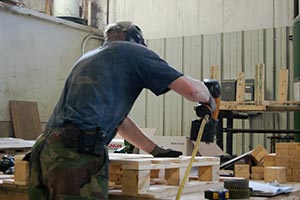 Photo of a guy making pallets with a nail gun.