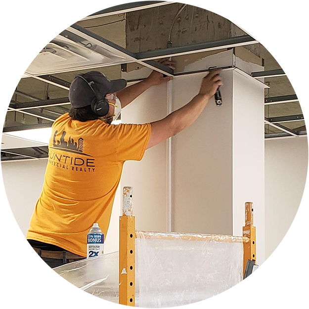 photo of a Suntide construction worker on a ladder, getting ready to add ceiling tiles