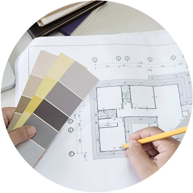 close up of a floor plan with a person's hand holding color samples and making notes on the page