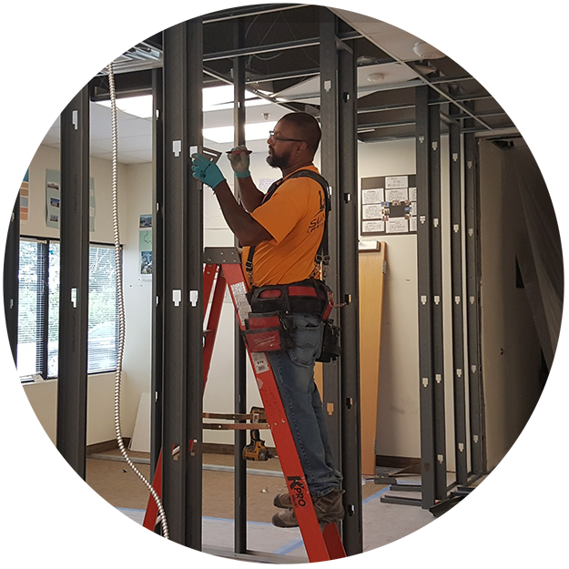 photo of a construction worker doing the initial framing of new office walls