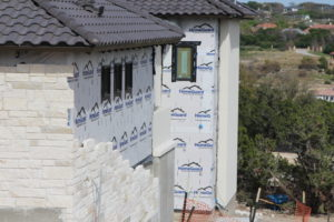 White limestone applied to a custom home in austin Texas with white mortar