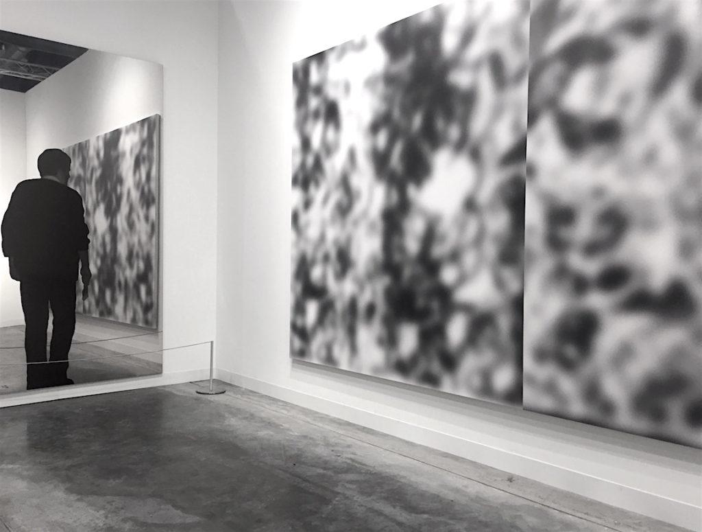 Far Left: Michelangelo Pistoletto, Pittore, 1962/1982, Silkscreen on polished stainless steel, , Far right: Jeff Elrod, Split-Screen Blur, 2016, UV Ink on Fischer canvas, Art Basel Miami, 2016, Photograph Katy Hamer