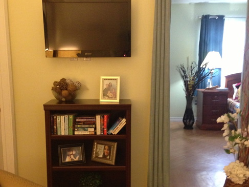 A bookcase and books with a wall mounted television next to a doorway.