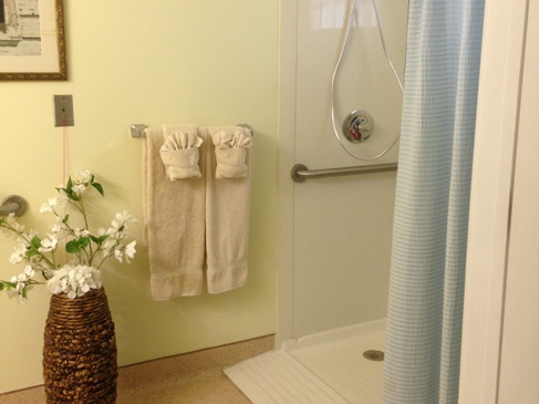 Azalea Gardens resort residence bathroom showing a walk-in shower, matching towels, and a wicker vase with white flowers.