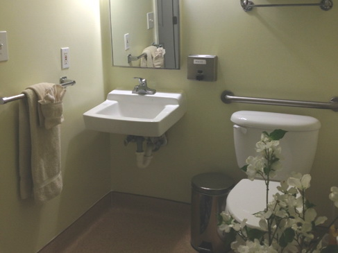 Azalea Gardens resort residence bathroom showing a sink and toilet, with towels and flowers.