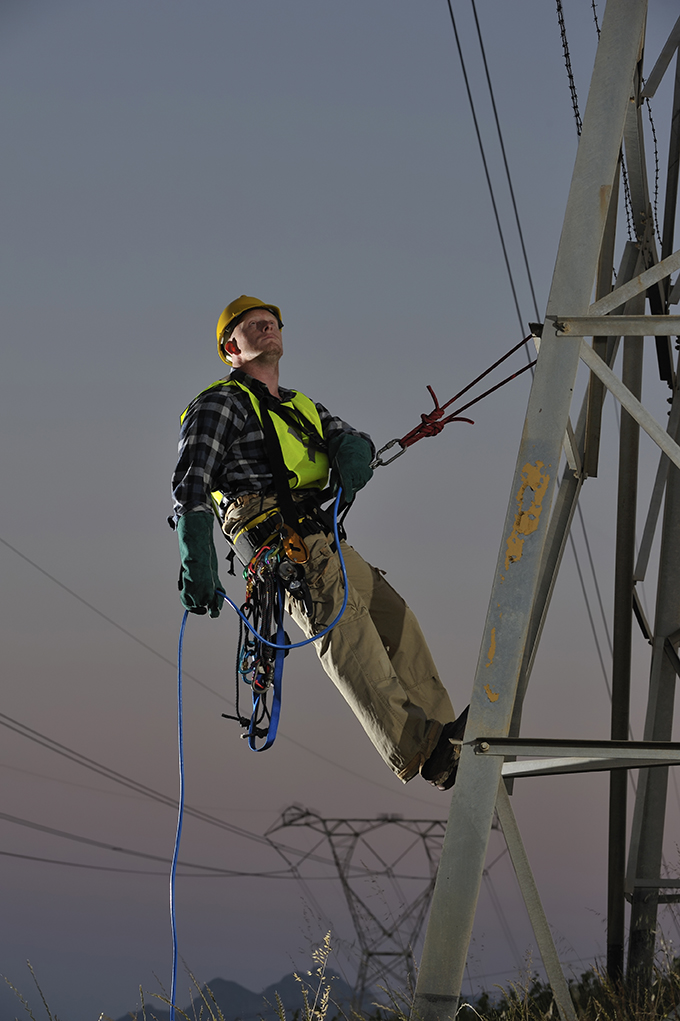 Power utility worker abseiling from pylons