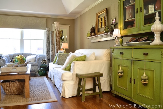 White slipcovered sofas with green painted cabinet