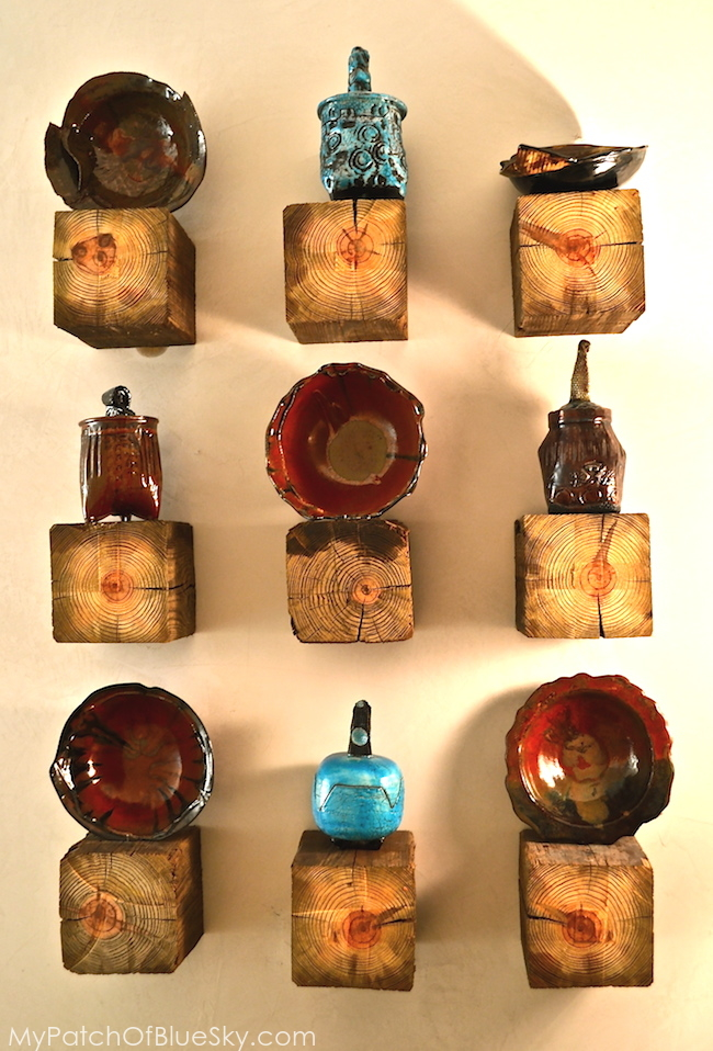 North Carolina pottery displayed on chunky wood shelves.