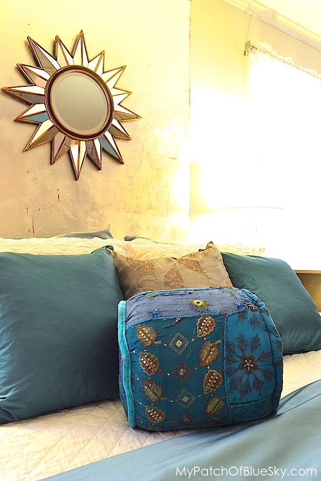 Silver leaf wall with teal pillows