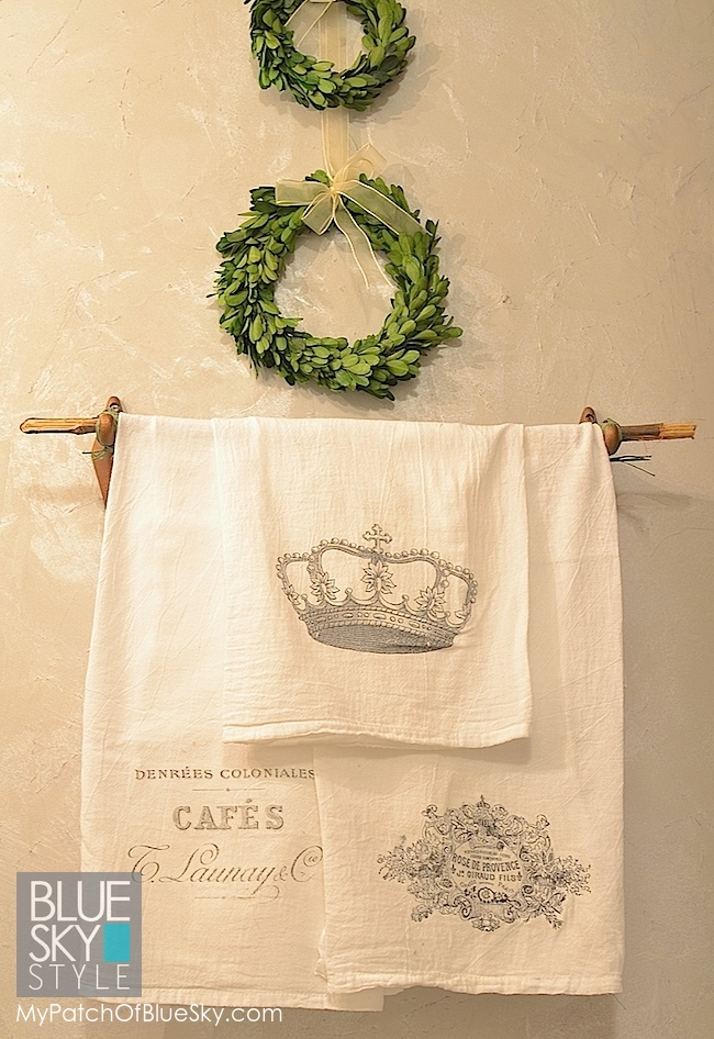 Lustrous white walls are a lovely backdrop to simple boxwood wreaths and soft towels.