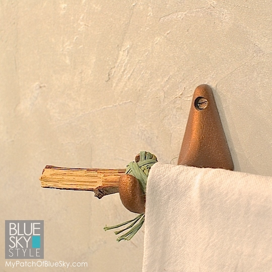 A broken branch from the yard, paired with junk drawer hardware and raffia make an interesting towel bar in a tiny powder room.