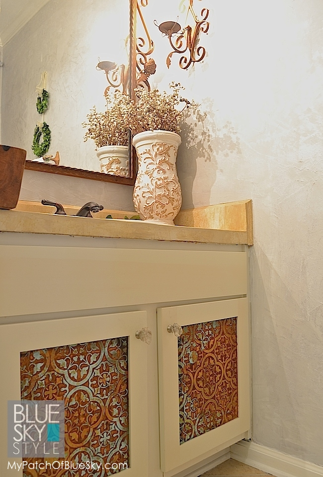 This tiny powder room got a rustic redo, including patterned, patina cabinet panels.