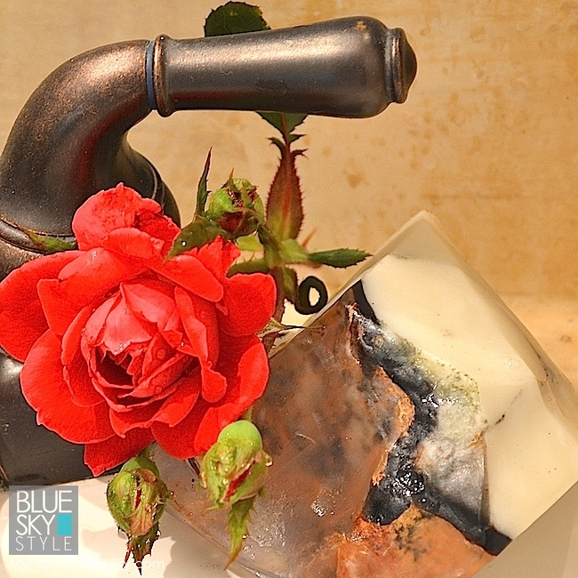 An artsy chunk of handmade rock soap, paired with a small rose from the yard add elegance to a tiny powder room.