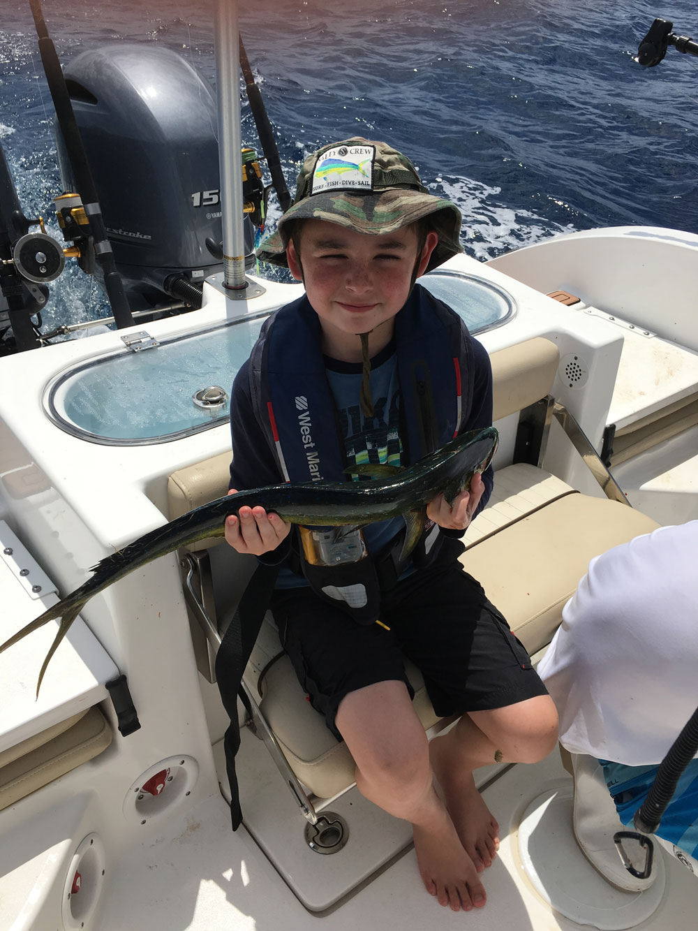 Boy sitting on the boat with dark colored fish in hands