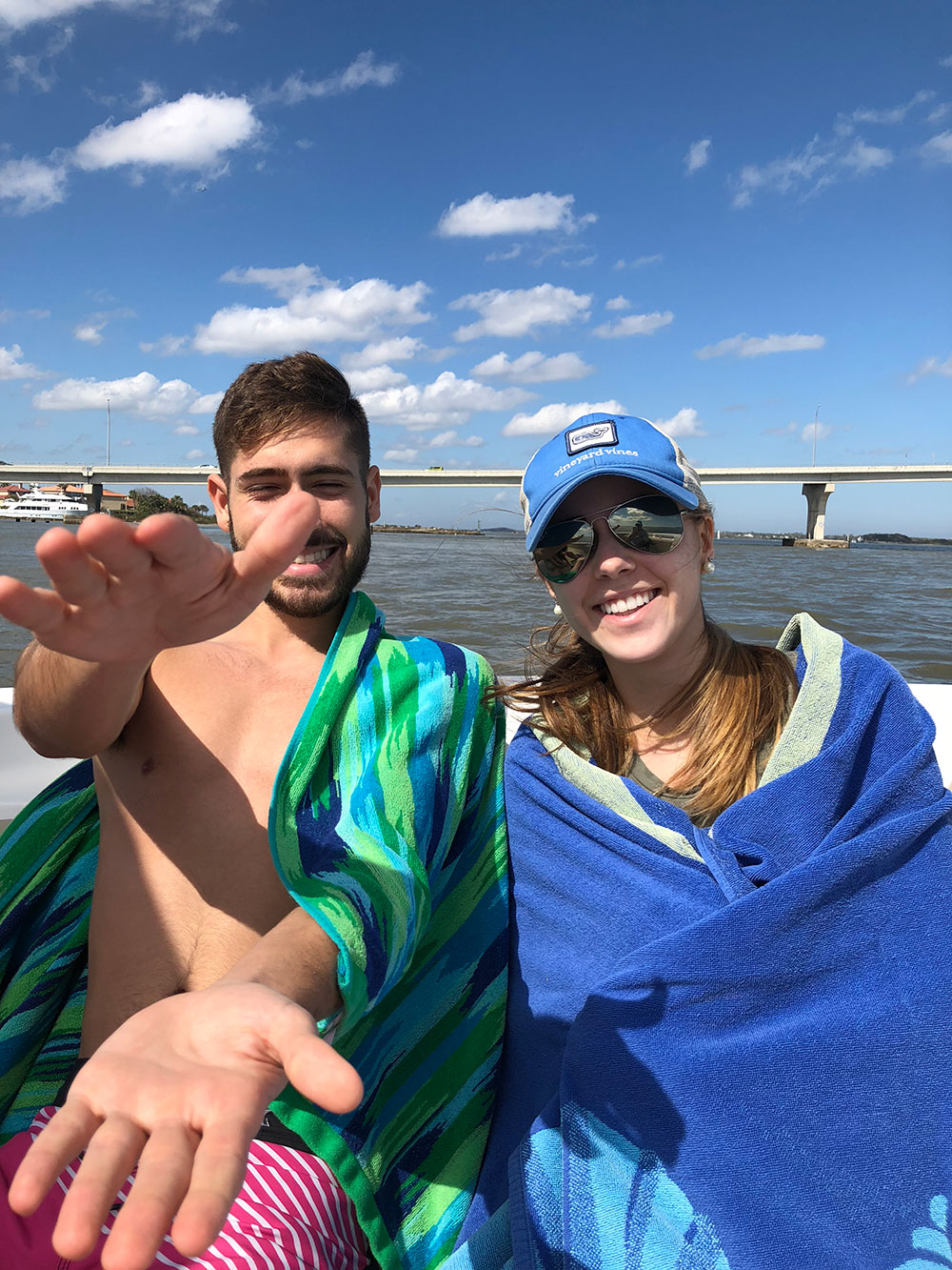 Teenage boy making alligator hand gesture sitting next to girl wrapped in a towel