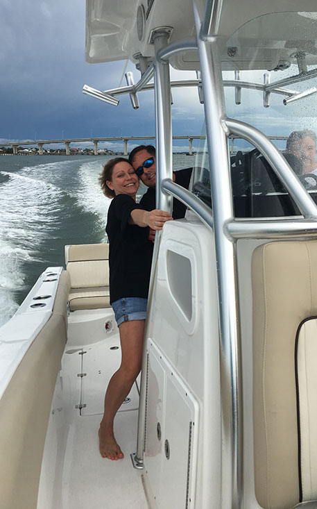 Man and woman smiling while enjoying a boat ride