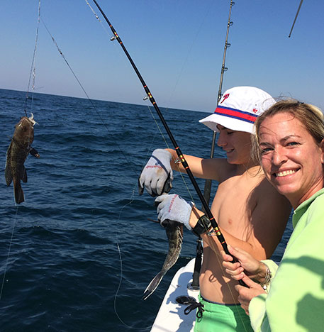 woman and boy with fishing poles reeling in a fish