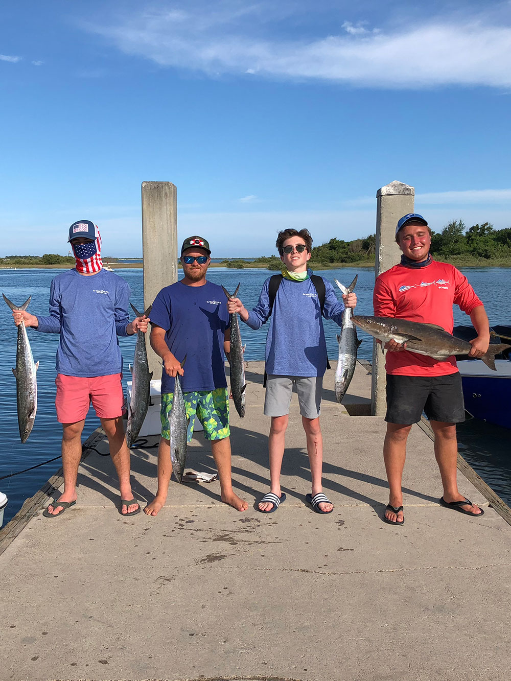 group of 4 men each holding fish while standing on a dock