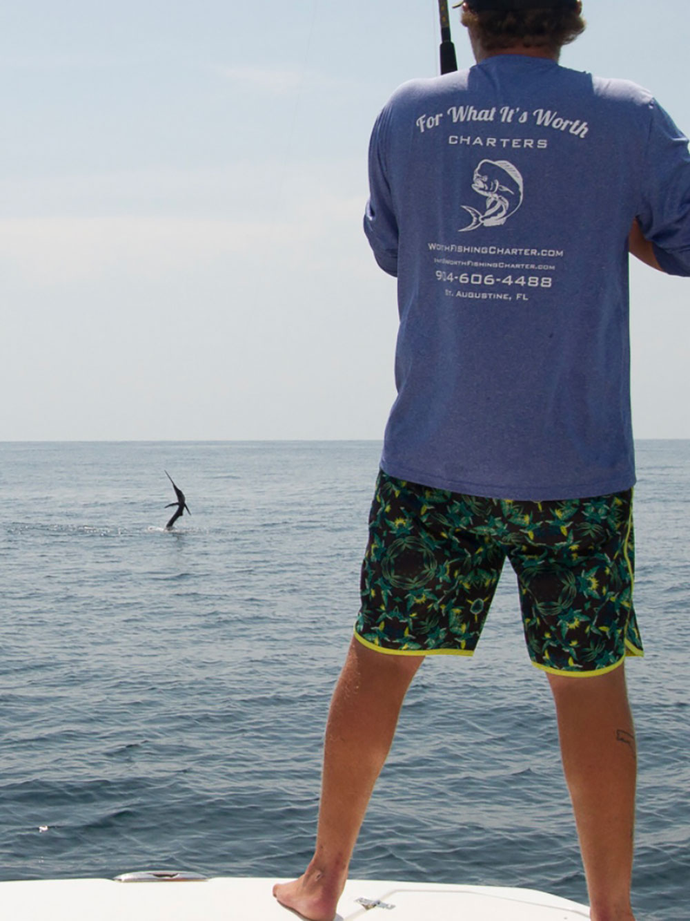man facing backward wearing For What It's Worth Charters shirt while standing on boat edge reeling in a fish