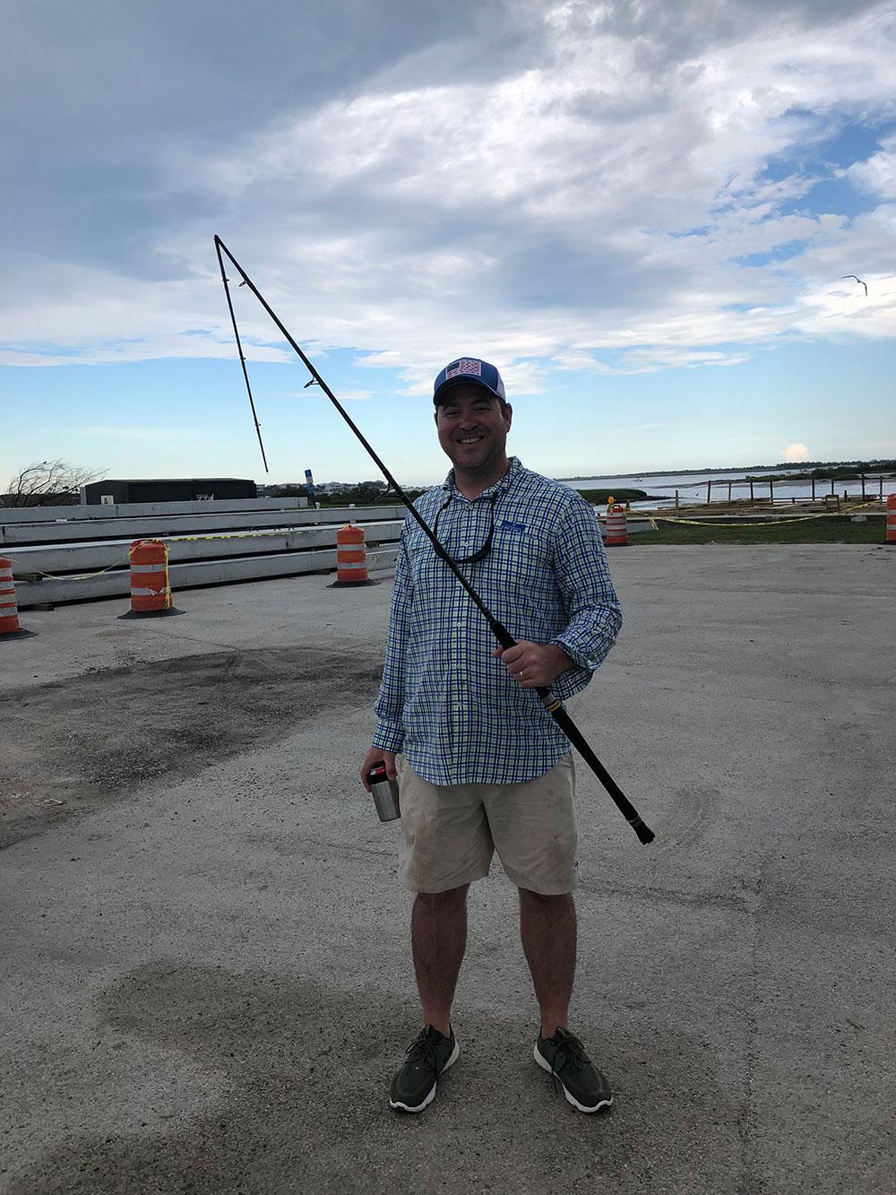 man holding fishing pole on dry land