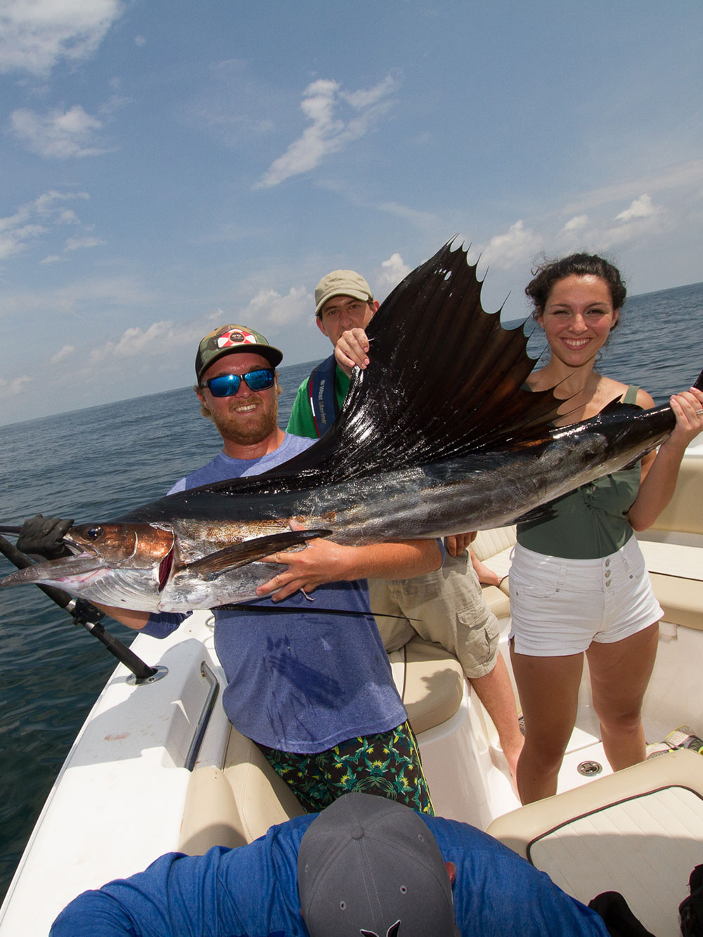 two people holding large fish with one person standing in the background all on a boat