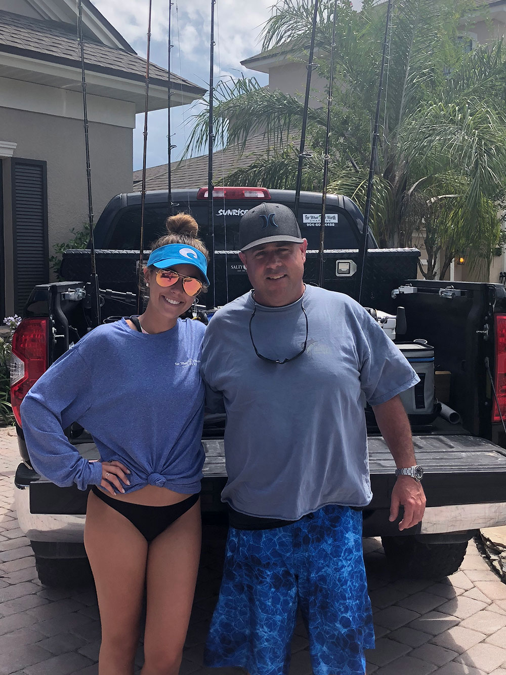 Hailee Worth and Chris Worth standing next to each other in front of fishing rods in a pick up truck