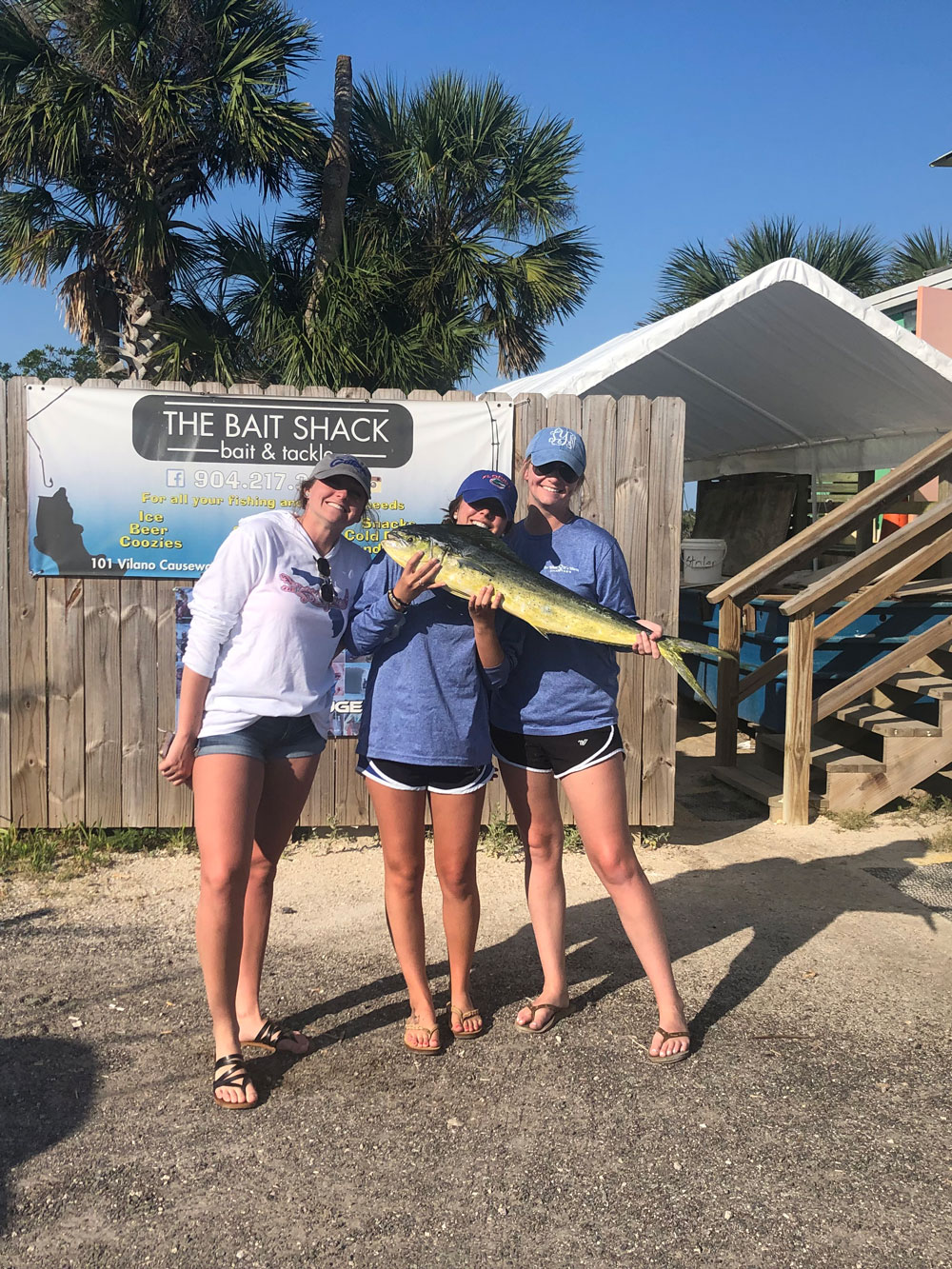 three ladies all holding one fish at The Bait Shack