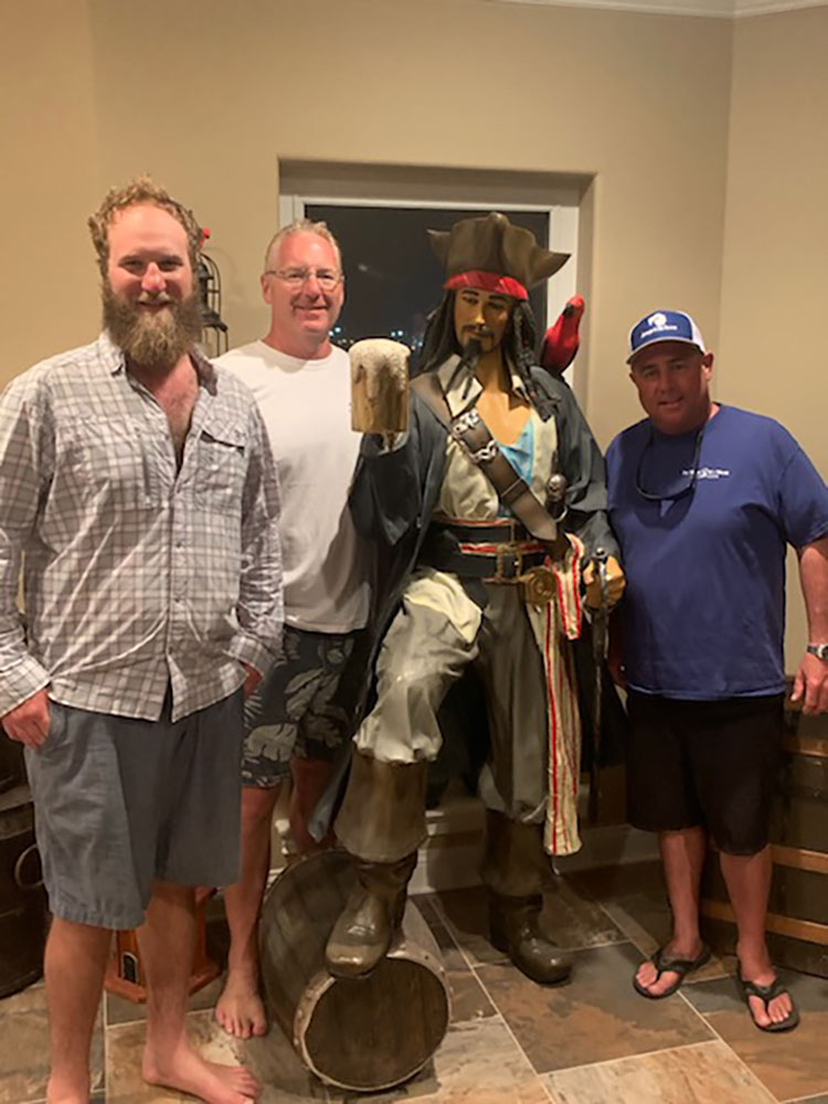 Chris Worth and guests standing next to a pirate statue