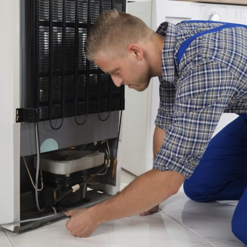 Young Male Repairman Making Refrigerator Appliance In Kitchen Room