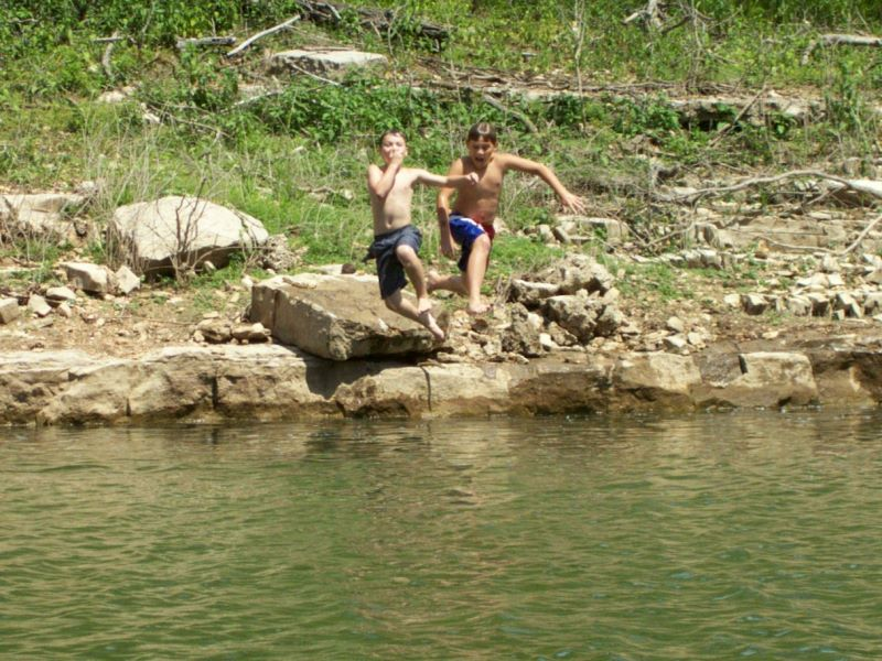 Boys jumping into the lake