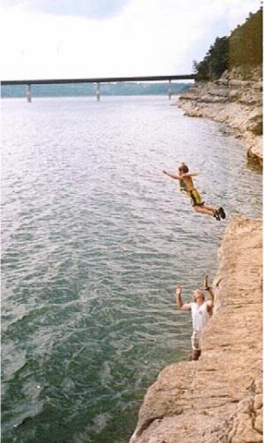 Boy jumping off cliff at norfork lake