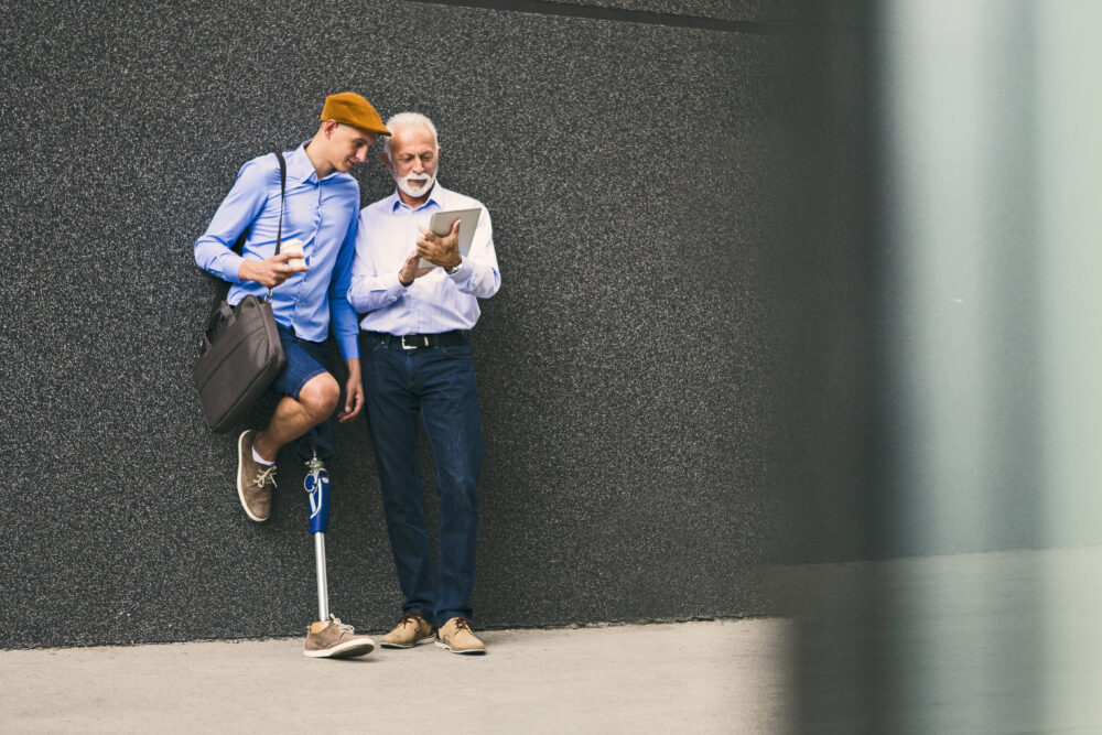 Young man with prosthetic leg posing in front of office building