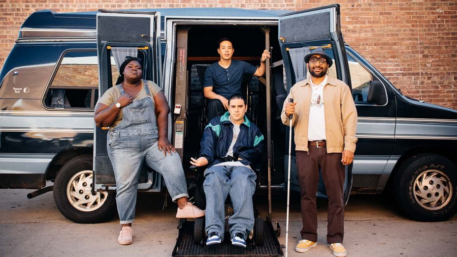 The stars of COME AS YOU ARE: Gabourey Sidibe (wearing overalls), Grant Rosenmeyer (in a blue and light blue jacket; in a wheelchair; on a ramp), Hayden Szeto (wearing a dark blue top; in a wheelchair; on a ramp), and Ravi Patel (in a light tan jacket, white shirt, and red jeans, holding a walker; on a ramp) posting in front of a van