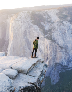A man stands on the edge of a cliff, looking down.