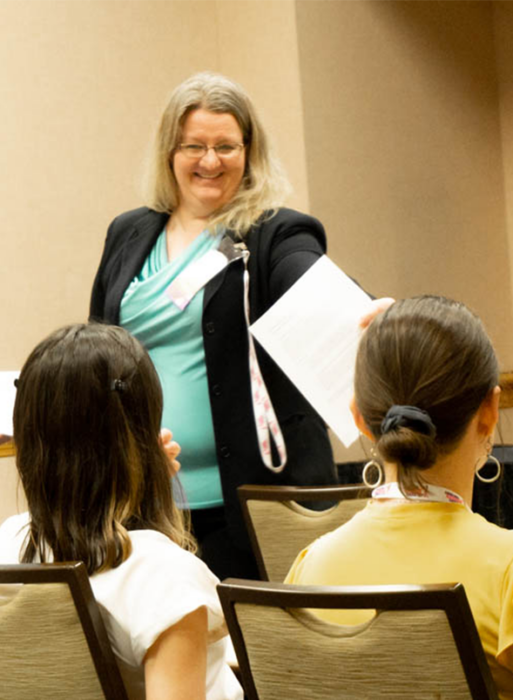 Tracy Costello during her talk at the 2020 Annual Life Science Women's Conference. She has blonde hair, is wearing a turqoise shirt and black blazer.