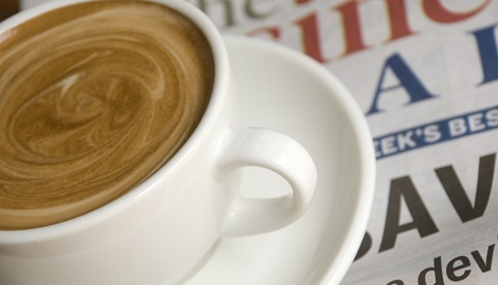 a coffee in a white cup and saucer shot on the business section of the newspaper