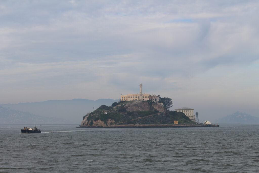 prison building on an island, boat passing by