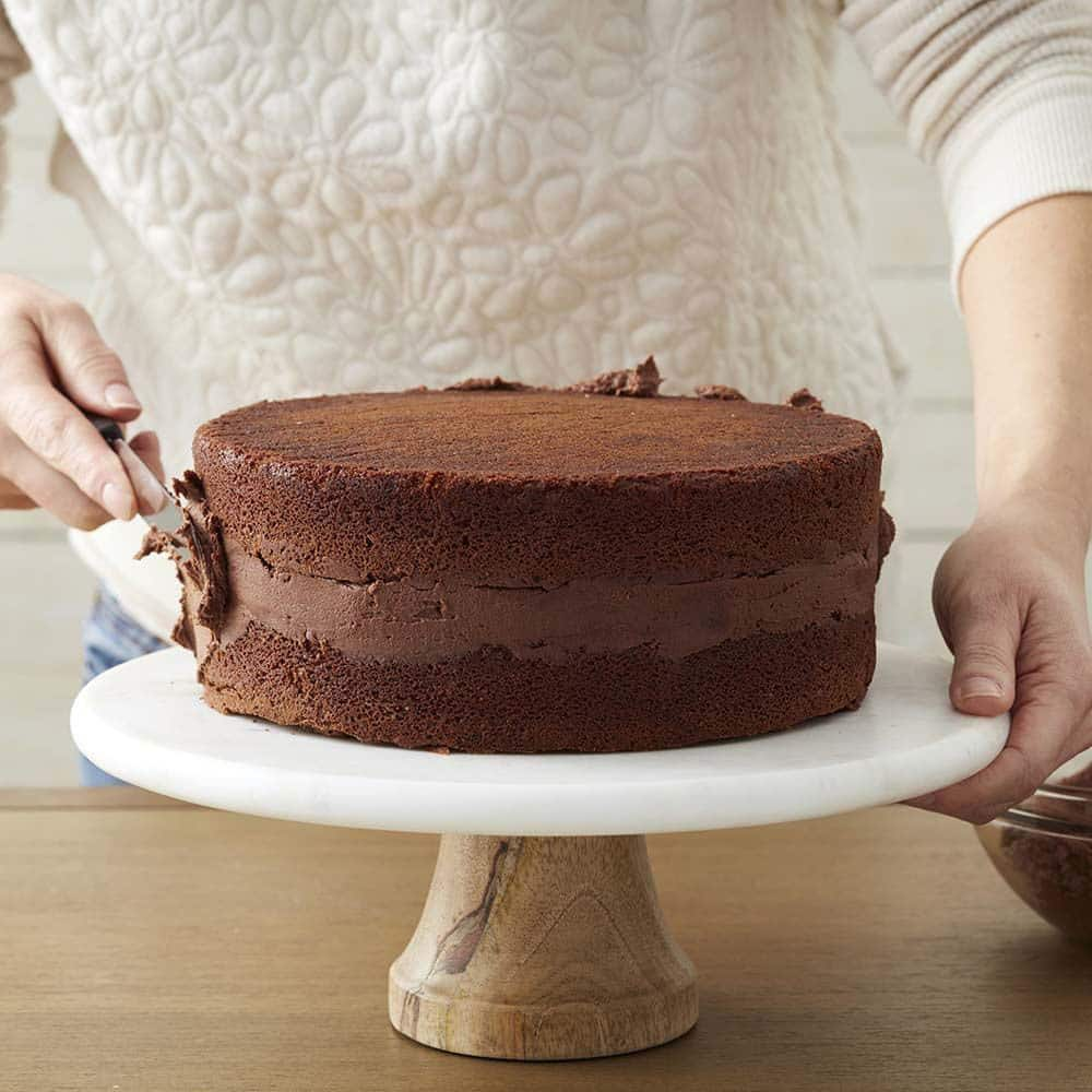 chocolate buttercream being spread on chocolate cake