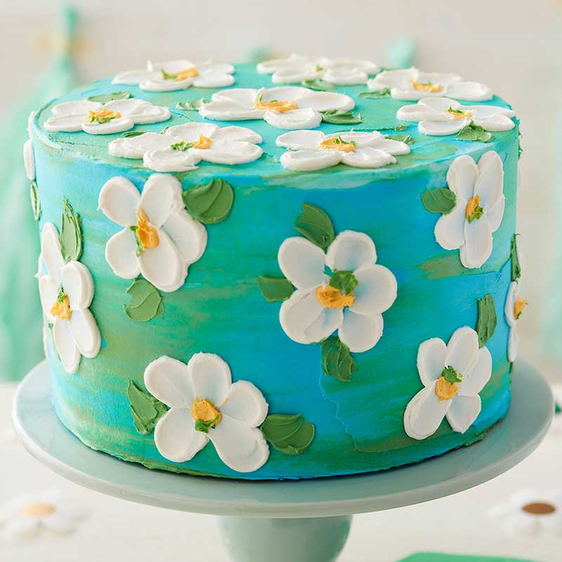 """Blue cake with """"painted"""" white buttercream flowers"""